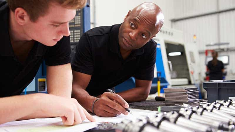 Two industry workers going over technical specs