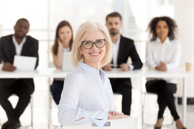 Business woman standing in front of her employees