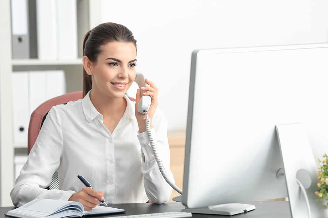 Women answering phone at receptionist desk