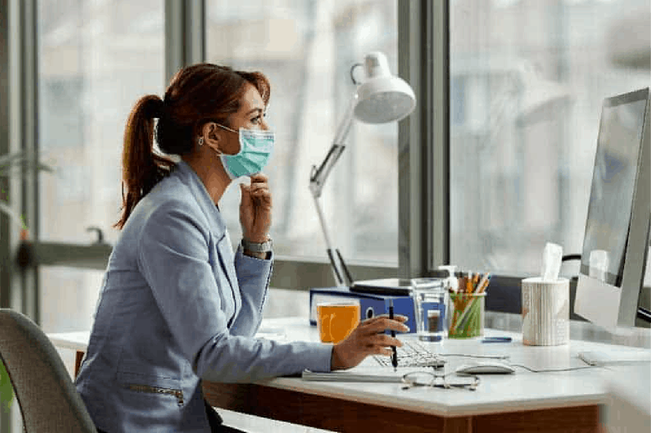 Female office worker at her desk wearing a mask